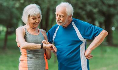 Elderly couple looking at activity tracking device