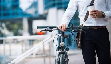 Man holding bike handlebars and a coffee cup