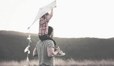 Dad and child flying a kite