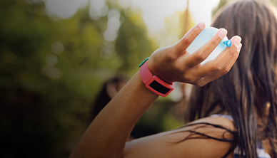 Decorative image of a woman wearing a Fitbit